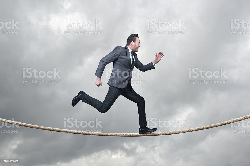 Businessman running on tightrope with stormy day stock photo