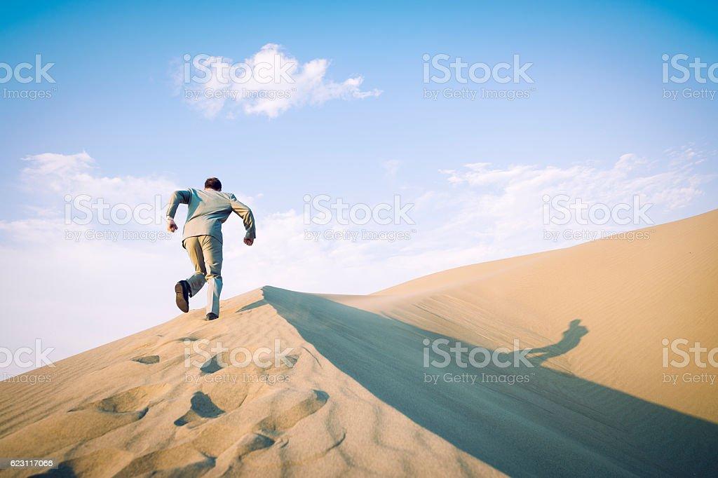 Businessman Running Up Desert Sand Dune stock photo