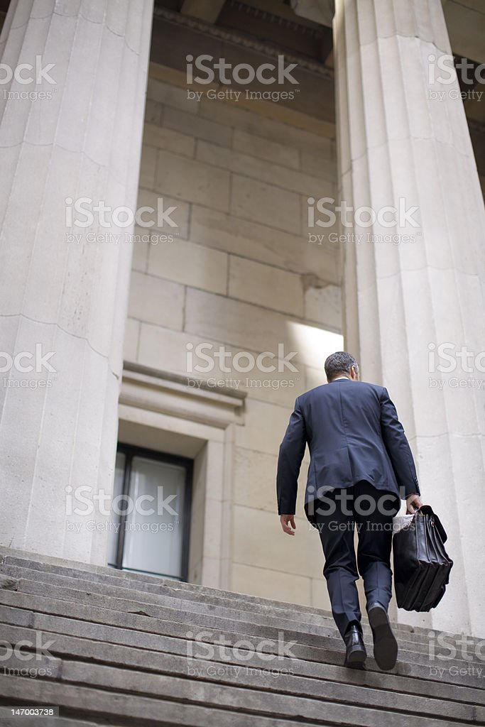 Businessman running up the steps of power royalty-free stock photo