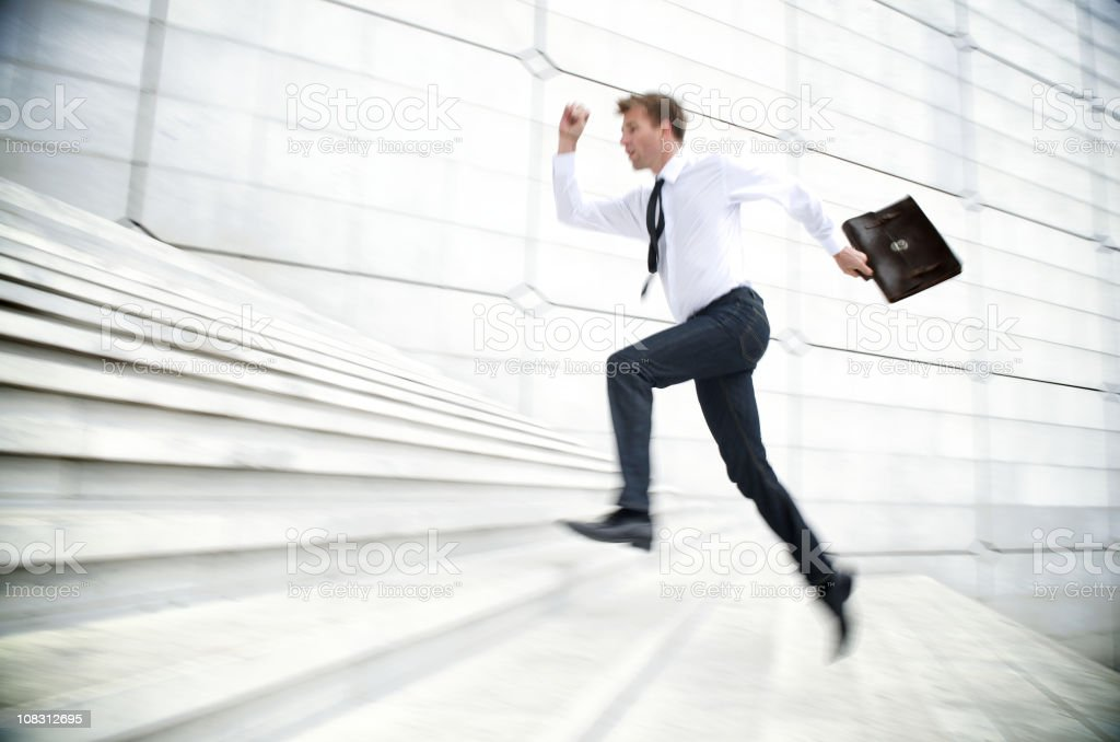 Businessman Running Up White Staircase stock photo