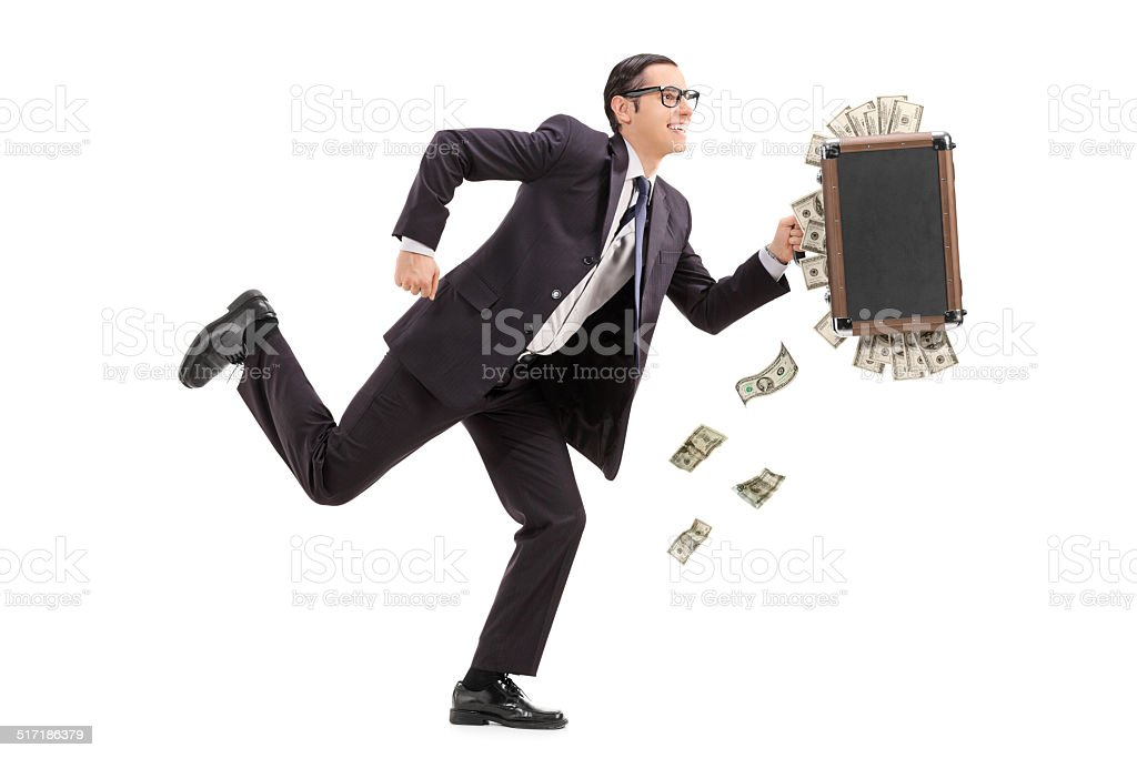 Businessman running with a bag full of money stock photo