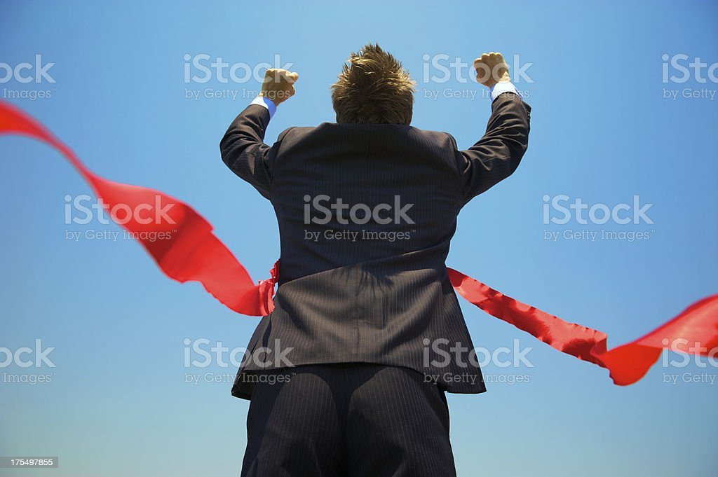 Businessman Runs Arms Up Through the Red Finish Line stock photo