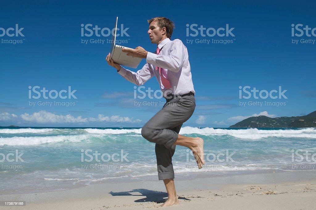 Businessman Runs on Beach w Laptop royalty-free stock photo