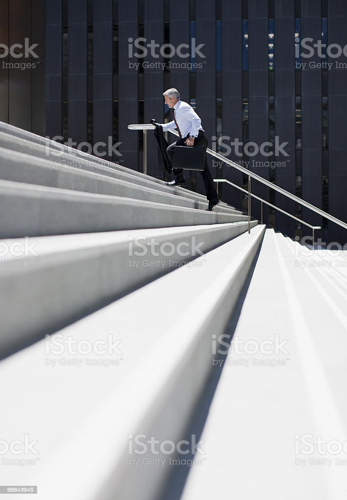 Businessman rushing up steps outdoors stock photo