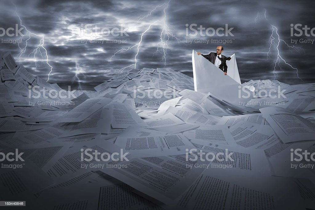 Businessman sailing in stormy papers sea royalty-free stock photo