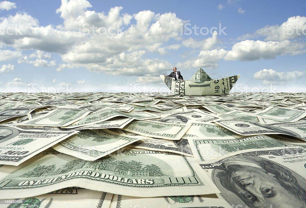 Businessman sailing on dollar boat stock photo