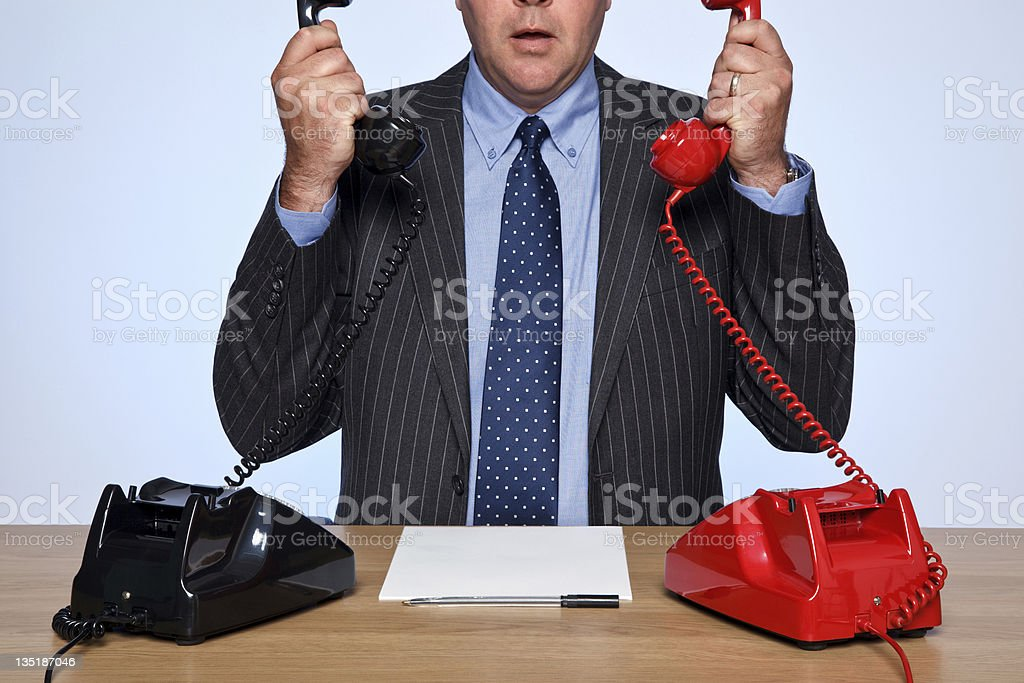 Businessman sat at desk with two telephones. royalty-free stock photo