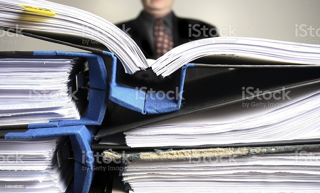Businessman saturated with paperwork stock photo
