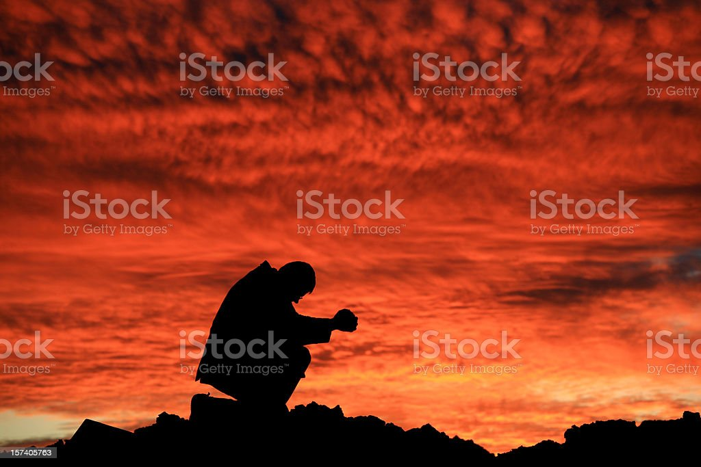Businessman Saying a Prayer at Sunset Silhouette royalty-free stock photo