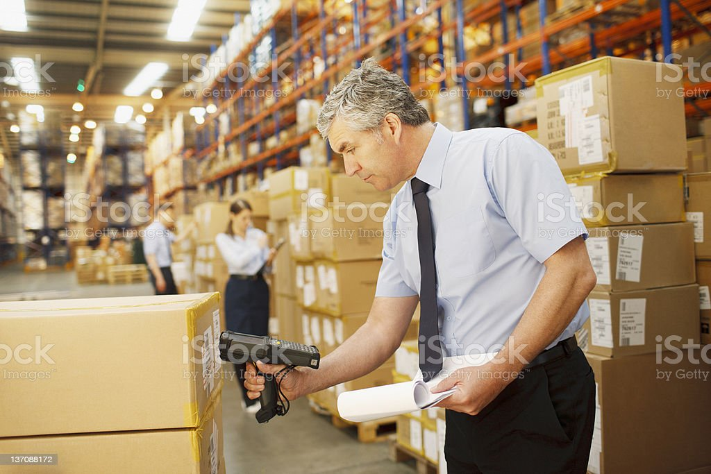 Businessman scanning shipping box in warehouse royalty-free stock photo