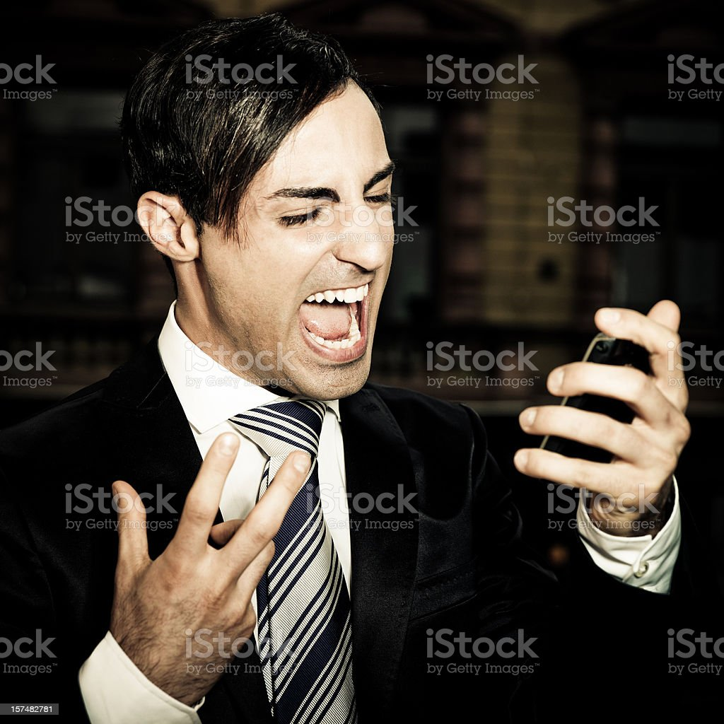 Businessman screaming into mobile phone royalty-free stock photo