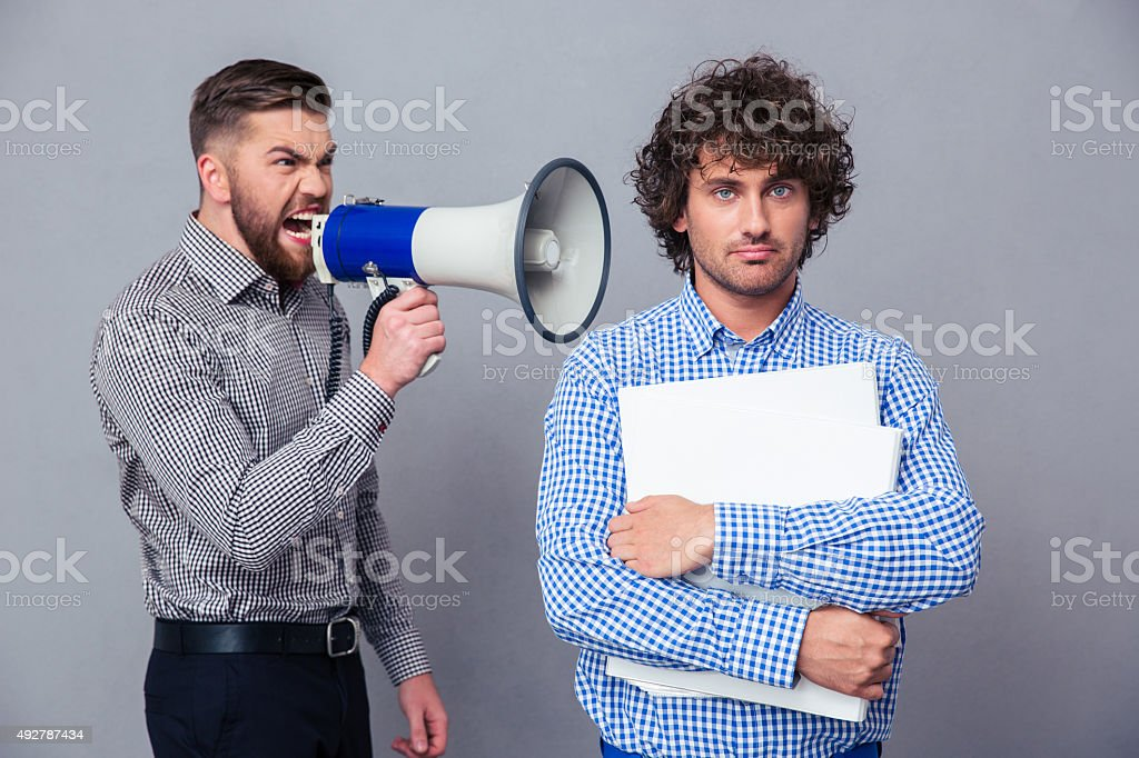 Businessman screaming via megaphone to another man stock photo