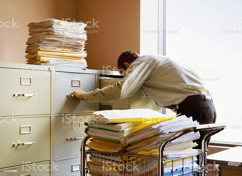 Businessman searching for documents in metal file cabinets. stock photo