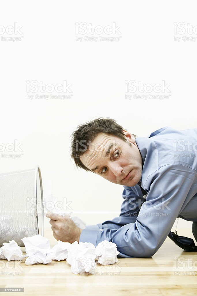 Businessman searching through garbage bin royalty-free stock photo