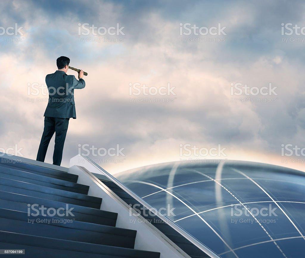 Businessman Searching Through Spyglass stock photo