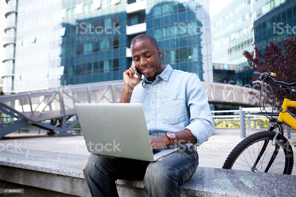 Businessman seated outside with computer and on phone stock photo