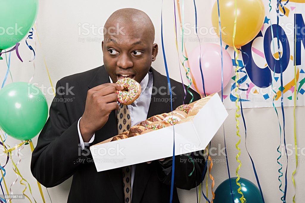 Businessman secretly eating doughnuts stock photo