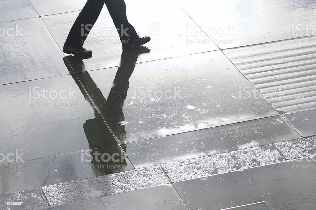 Businessman Shadow Reflects on Wet Stone Plaza stock photo