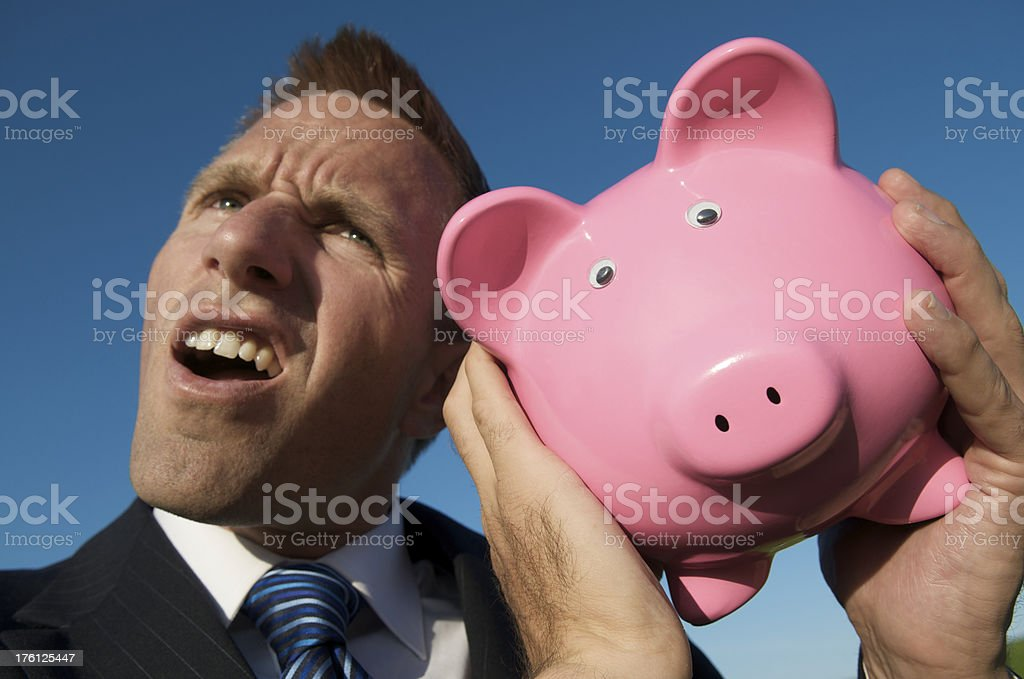 Businessman Shakes Pink Piggy Bank royalty-free stock photo
