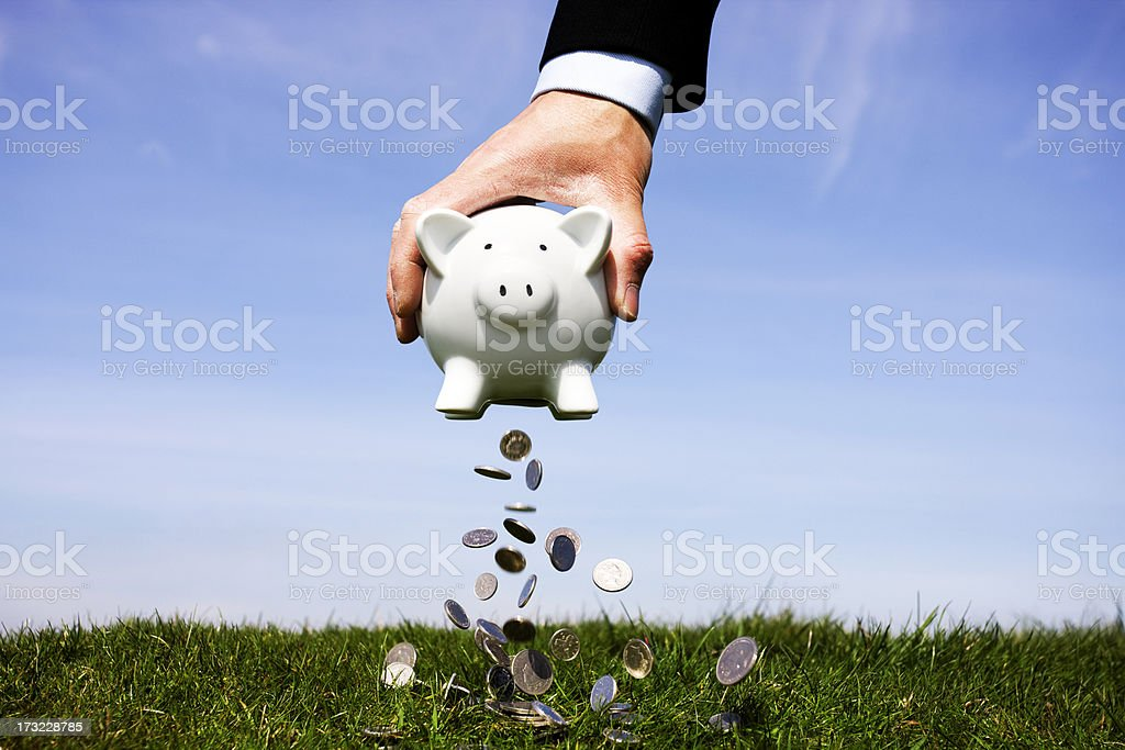 Businessman shaking a piggy bank stock photo