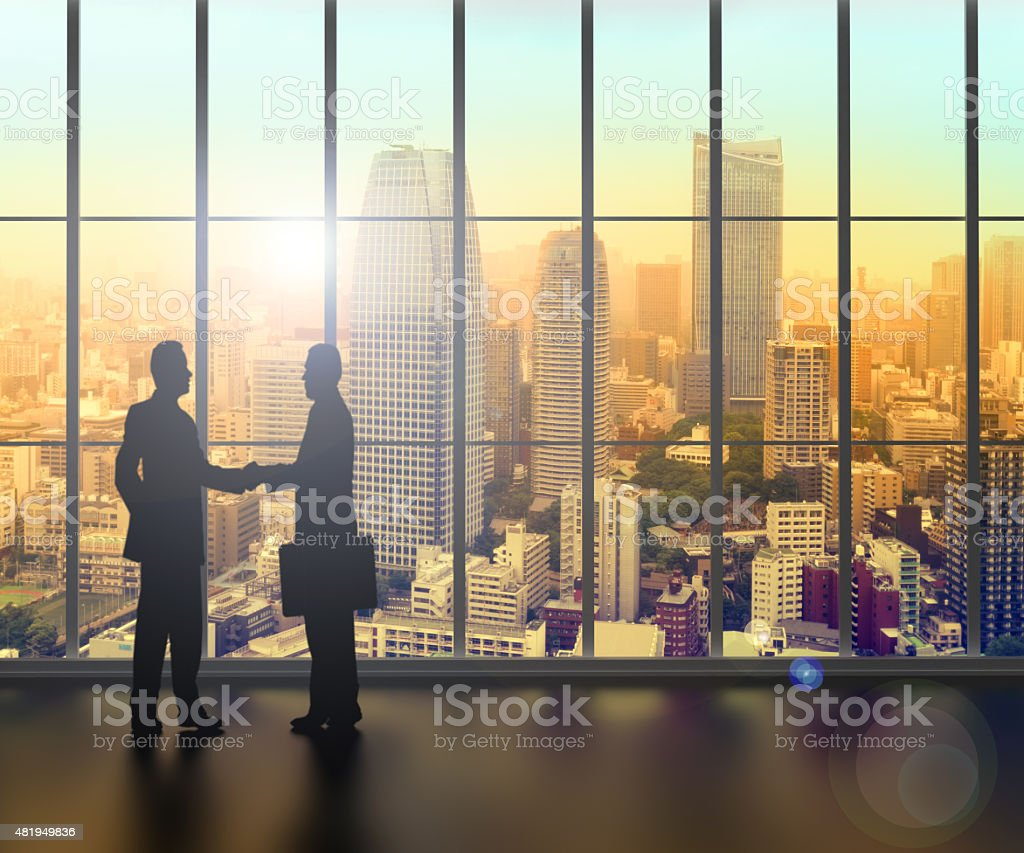 businessman shaking hands inside a business tower stock photo