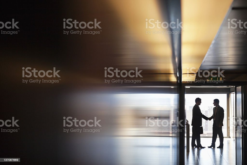 Businessman shaking hands together in corridor stock photo
