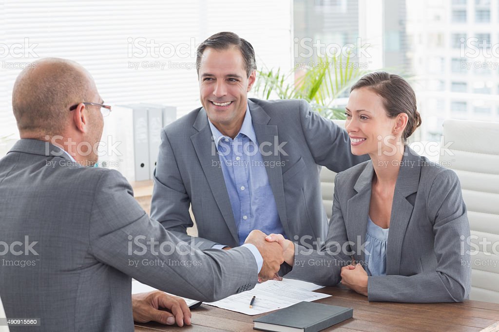 Businessman shaking hands with a businesswoman stock photo