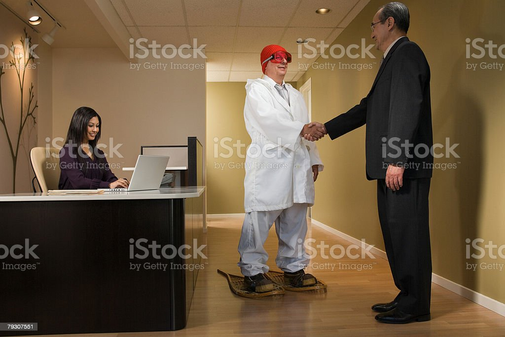 A businessman shaking hands with a man in snowshoes stock photo
