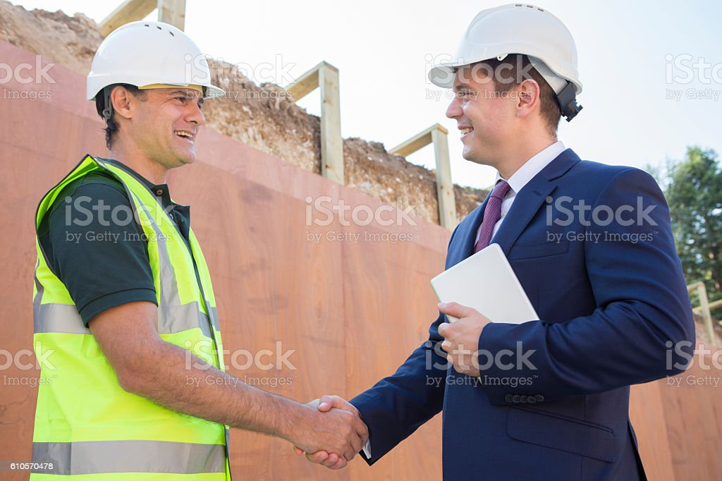 Businessman Shaking Hands With Builder On Construction Site stock photo