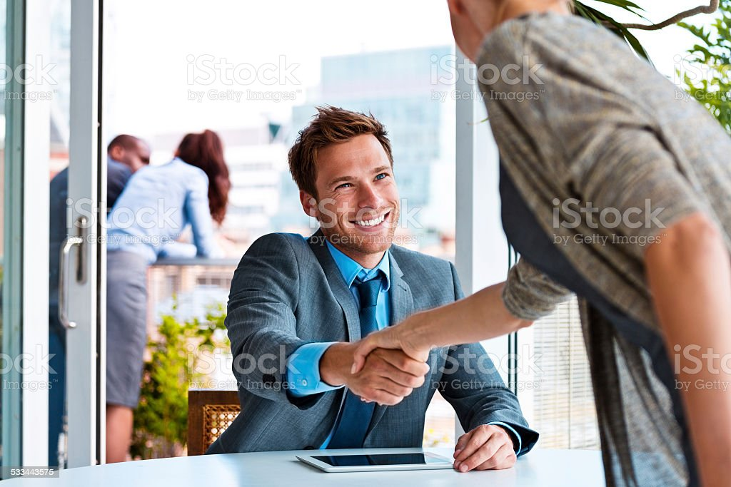 Businessman shaking hands with businesswoman stock photo