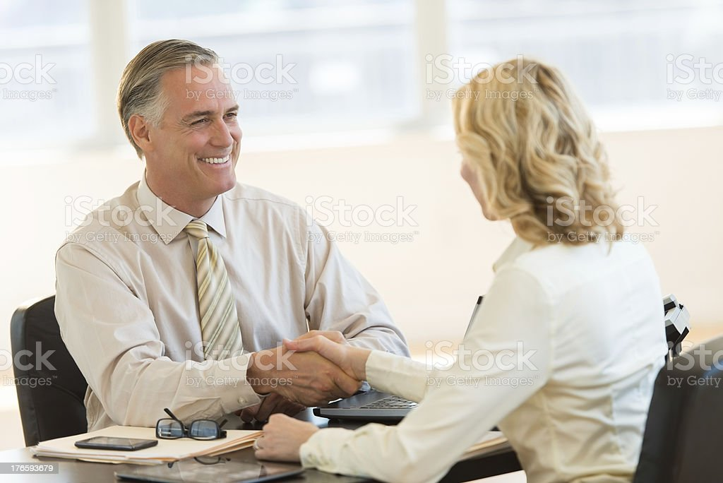 Businessman Shaking Hands With Colleague At Desk royalty-free stock photo