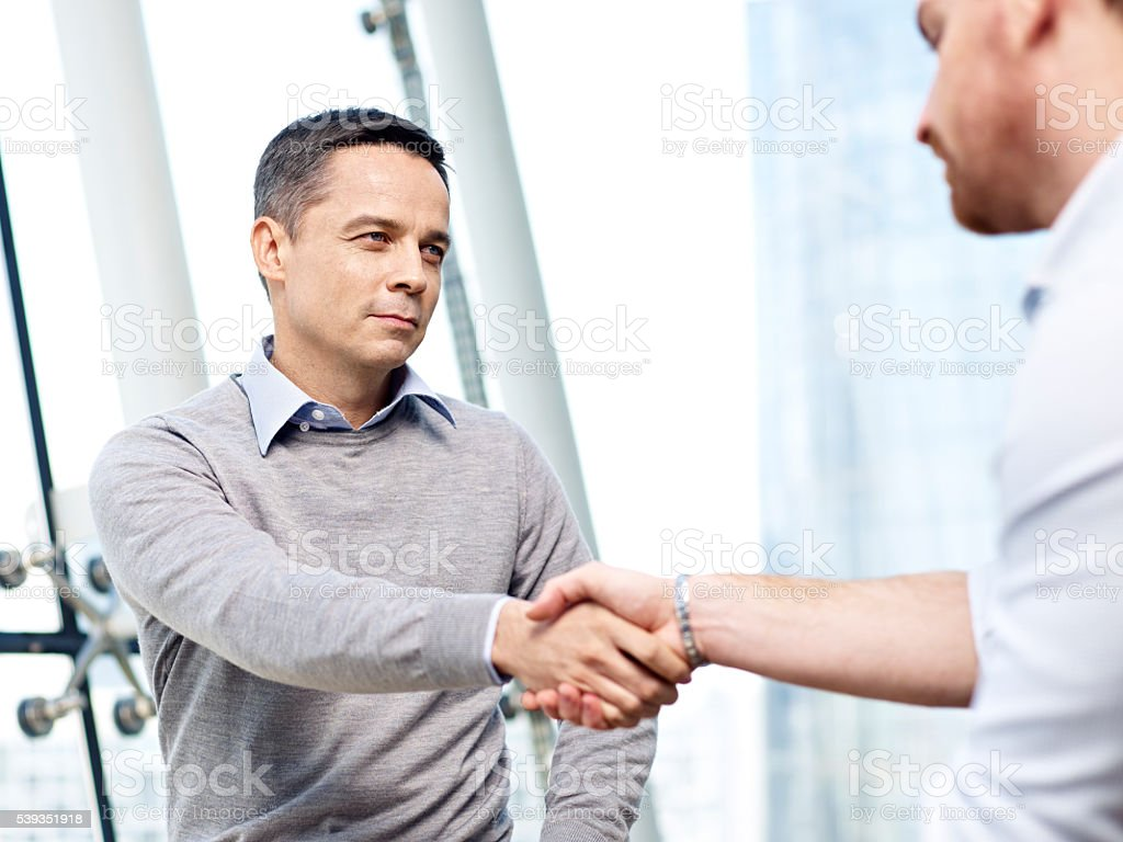 businessman shaking hands with competitor stock photo