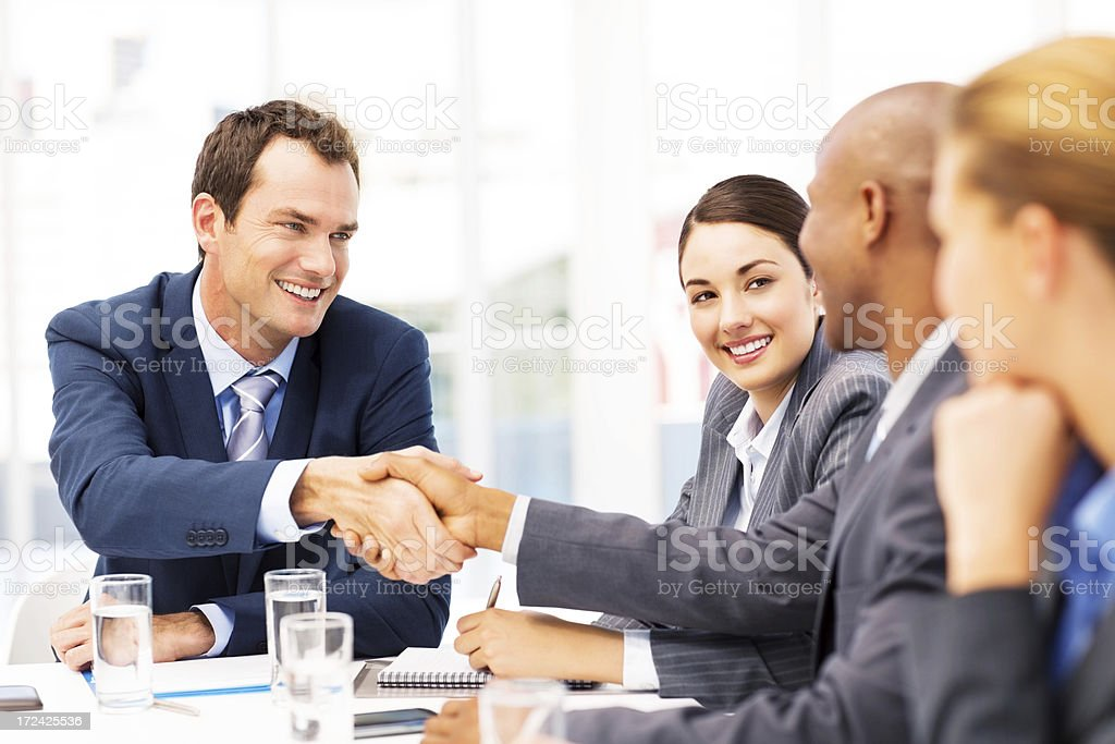 Businessman shaking hands with his team during a meeting royalty-free stock photo