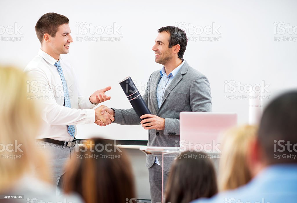 Businessman shaking hands with professor and receiving a diploma. stock photo