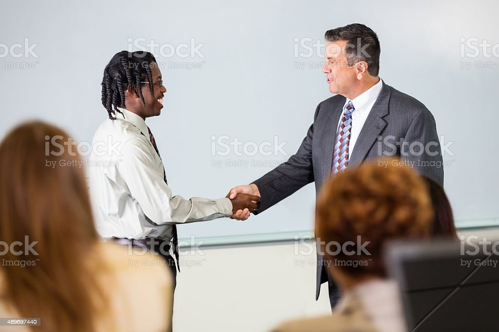 Businessman shaking hands with student during conference stock photo