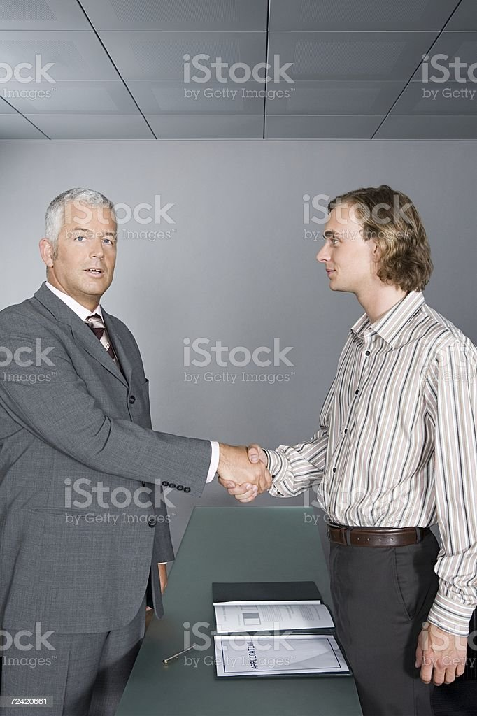 Businessman shaking hands with  young man royalty-free stock photo