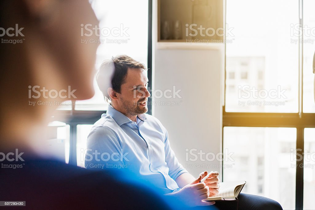 Businessman sharing ideas in meeting room stock photo