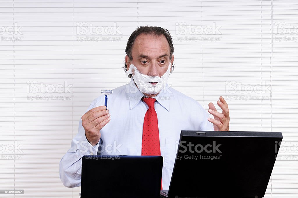 Businessman Shaving while Looking At PC royalty-free stock photo