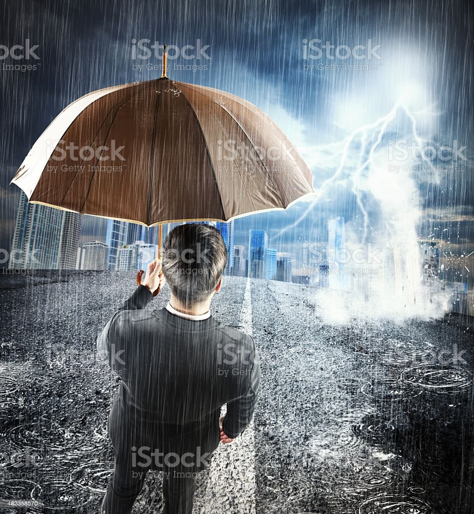 Businessman sheltering from problem stock photo