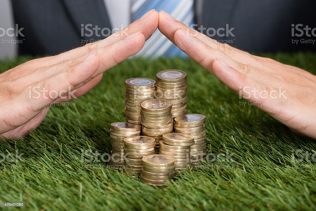 Businessman Shielding Stacked Coins On Grass stock photo