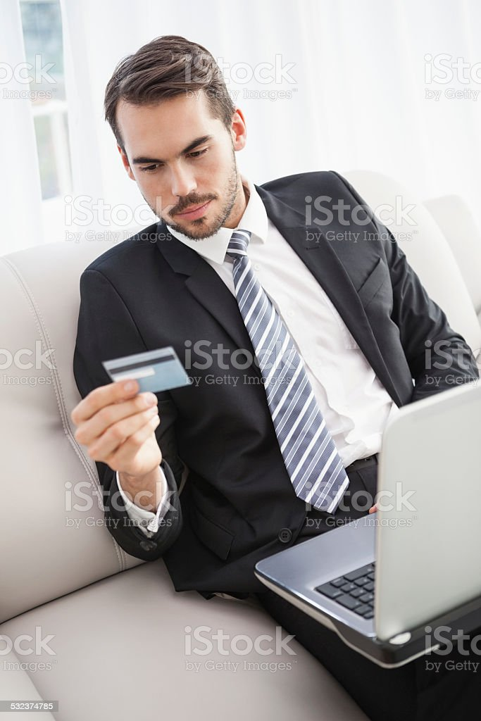 Businessman shopping online on his couch stock photo