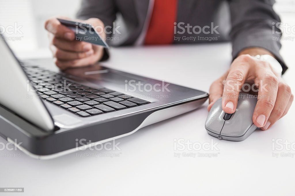 Businessman shopping online on laptop stock photo