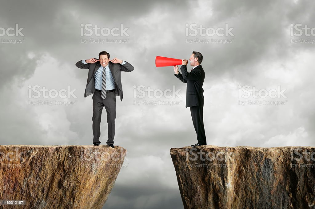 Businessman shouting at another businessman through a megaphone stock photo