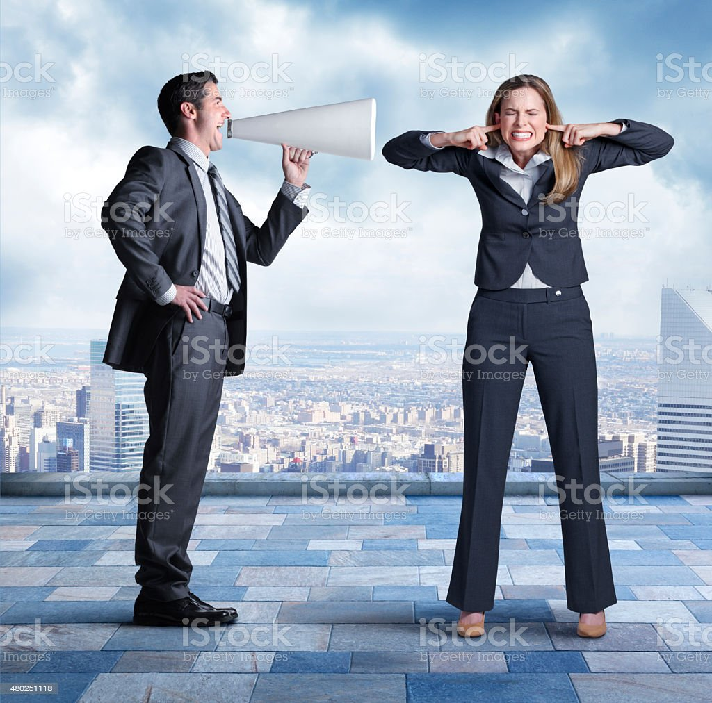 Businessman Shouting At Businesswoman Through Megaphone stock photo