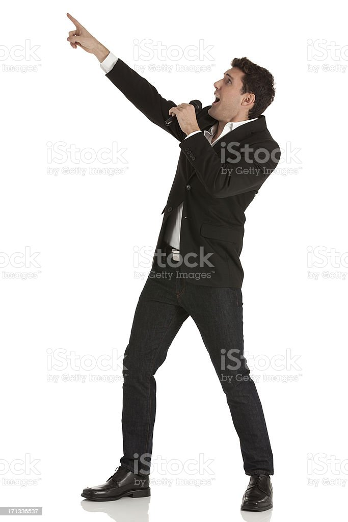 Businessman shouting into a microphone and pointing royalty-free stock photo
