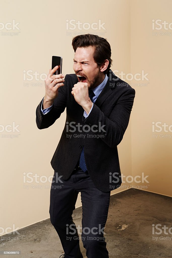 Businessman shouting into cell phone, studio stock photo