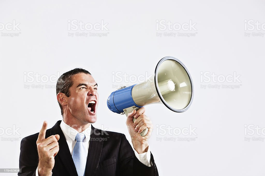 Businessman shouting into loud hailer energetically royalty-free stock photo
