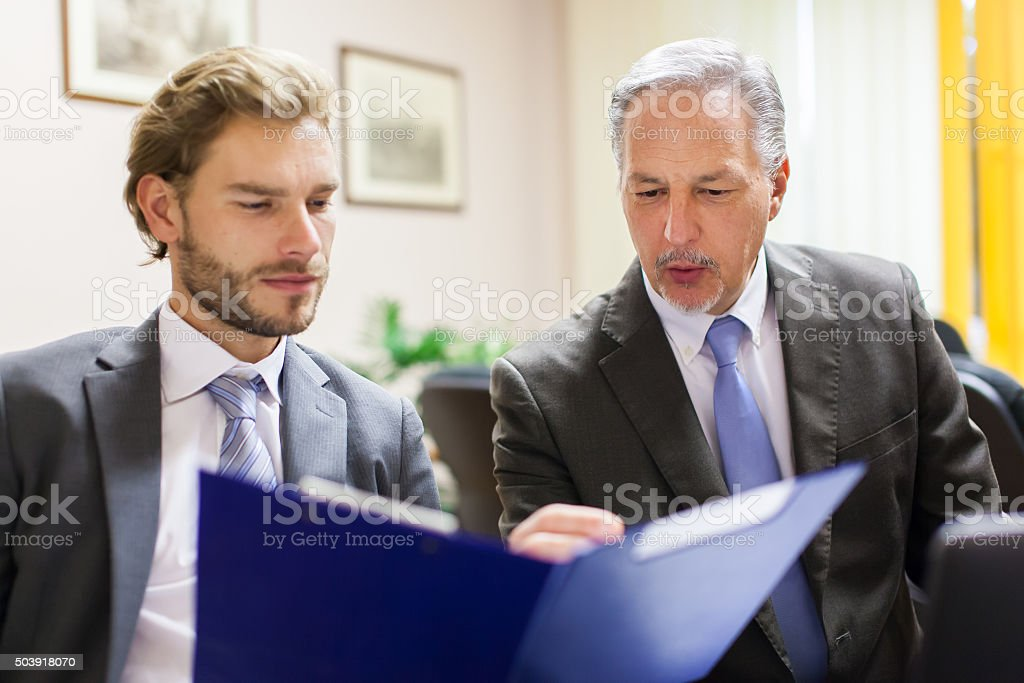 Businessman showing a document to his colleague stock photo