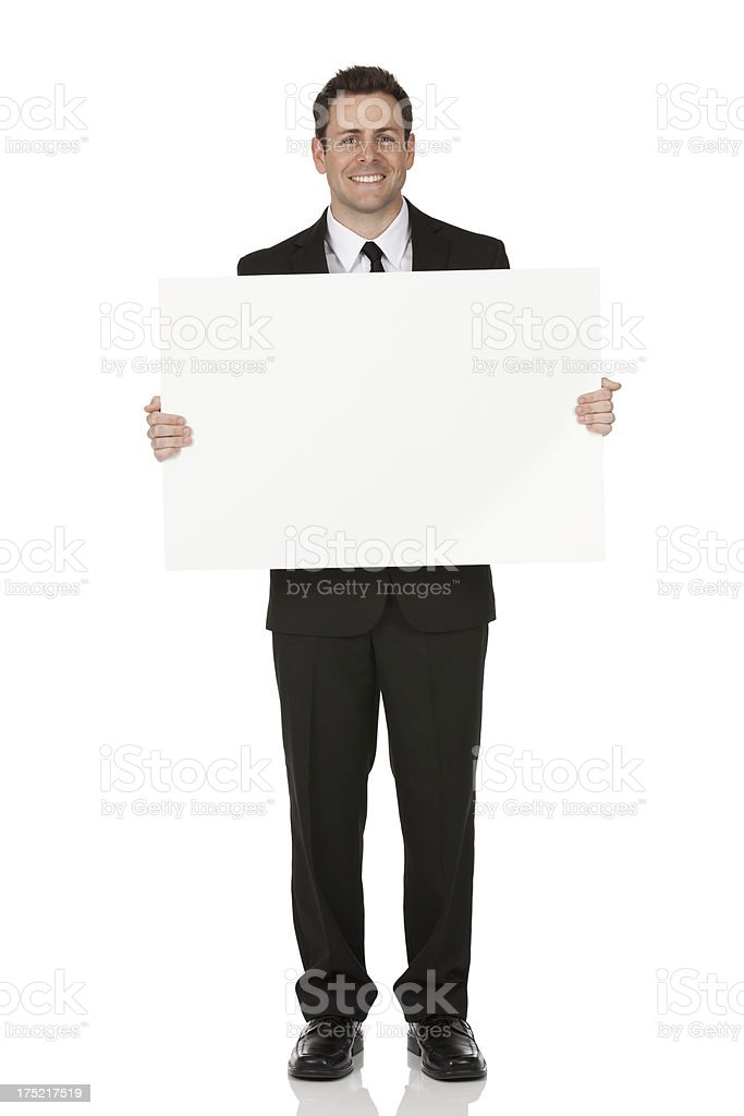 Businessman showing a placard and smiling royalty-free stock photo
