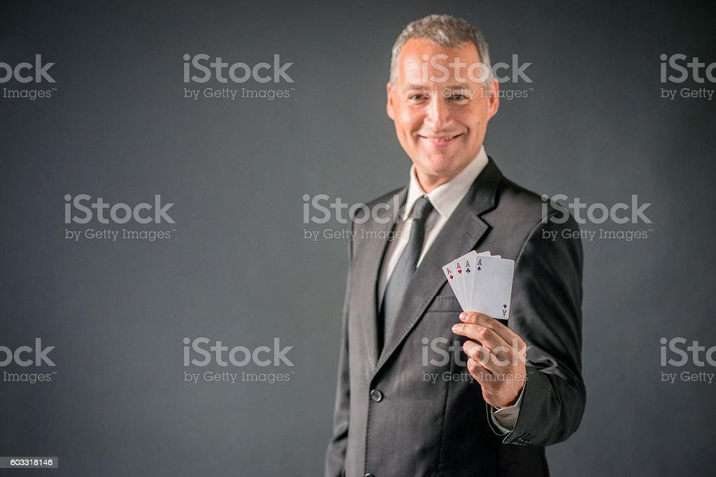 Businessman Showing Card Hand of Aces over gray background stock photo